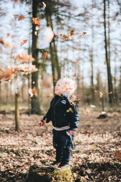 A little boy jumps and plays in fall leaves. This article covers fun outdoor play ideas that nurture imagination and creativity.