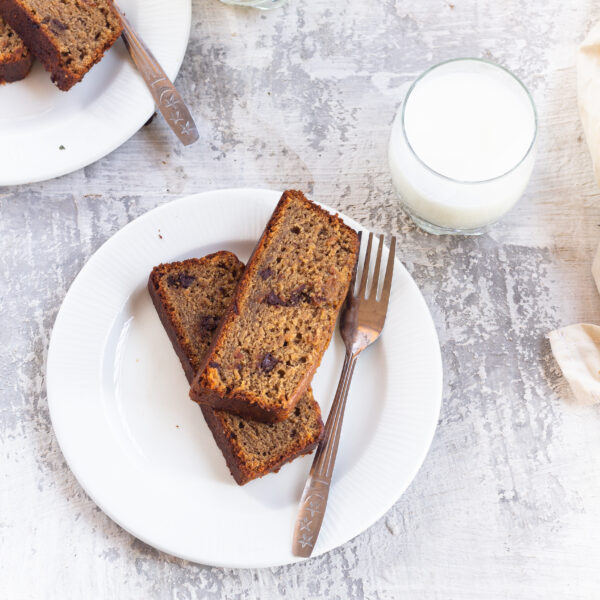 Banana bread slices are on plates with a fork. There are two glasses of milk. This article shares the Super Moist Banana Bread recipe from the How-To Cookbook for Kids.